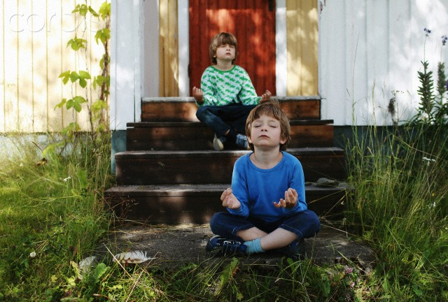 25 Jul 2012 --- Two boys sitting cross legged on steps meditating --- Image by © Marc Fluri/Corbis